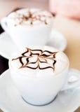与巧克力设计的两杯意大利热奶咖啡 库存图片