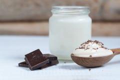 与巧克力酸奶家的酸奶 背景玉米片食物健康宏观工作室白色 免版税库存图片