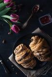 与巧克力釉的新鲜的新月形面包在早餐 库存照片
