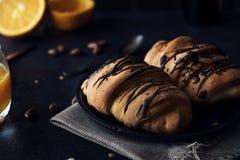 与巧克力釉的新鲜的新月形面包在早餐 免版税库存图片