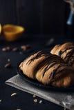 与巧克力釉的新鲜的新月形面包在早餐 库存图片