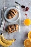 与巧克力釉的新鲜的新月形面包在早餐 免版税图库摄影