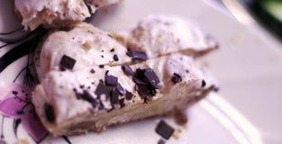 与巧克力顶部的小饼在一块白色板材 免版税库存图片