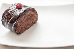 与巧克力结冰的巧克力蛋糕在白色板材 库存照片