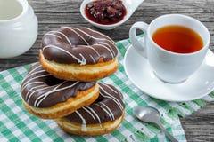 与巧克力结冰的油炸圈饼,一杯茶,特写镜头 免版税库存照片