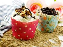 与巧克力结霜的巧克力杯形蛋糕反对背景 免版税库存图片