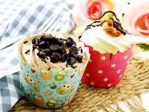与巧克力结霜的巧克力杯形蛋糕反对背景 免版税库存照片