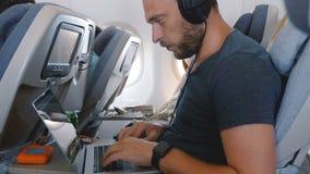 与巧妙的手表的年轻愉快的被聚焦的自由职业者的商人使用膝上型计算机工作在移动式办公室在平面飞行期间 股票录像