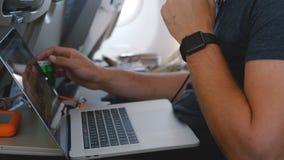 与巧妙的手表的特写镜头年轻自由职业者的商人使用膝上型计算机工作在网上在飞机出差飞行期间 股票录像