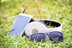 与巧妙的电话和耳机的玻璃在草甸 免版税库存图片