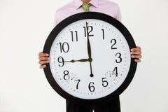 与巨型时钟的新生意人 图库摄影