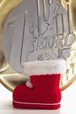 与巨大的一枚欧洲硬币的圣诞老人起动在背景中 免版税库存图片