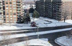 与巨大的窗口和阳台的现代公寓房大厦和积雪的清除拖拉机在蒙特利尔 免版税库存照片