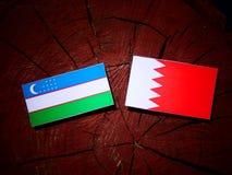 与巴林旗子的乌兹别克斯坦旗子在被隔绝的树桩 免版税库存图片