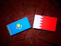 与巴林旗子的哈萨克斯坦旗子在被隔绝的树桩 图库摄影