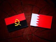 与巴林旗子的安哥拉旗子在被隔绝的树桩 免版税库存图片