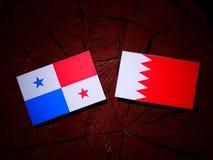 与巴林旗子的巴拿马旗子在树桩 库存图片