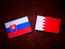 与巴林旗子的斯洛伐克的旗子在被隔绝的树桩 库存照片