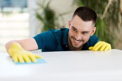 与布料的微笑的人清洁桌在家 免版税库存图片