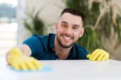 与布料的微笑的人清洁桌在家 库存照片