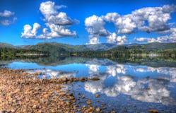 与帆船的清楚的镇静平安的水在有小山的一个湖和cloudscape在夏天HDR 库存照片