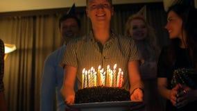 与带来生日蛋糕的朋友的愉快的男性给您 党的幸福 股票录像