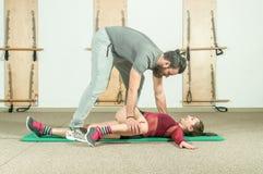与帮助年轻健身女孩的胡子的英俊的男性个人教练员在坚硬训练锻炼, selecti以后舒展她的肌肉 库存照片