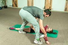 与帮助年轻健身女孩的胡子的英俊的男性个人教练员在坚硬训练锻炼, selecti以后舒展她的肌肉 免版税图库摄影