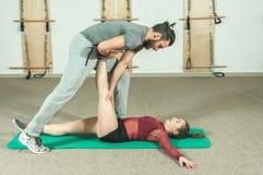 与帮助年轻健身女孩的胡子的英俊的男性个人教练员在坚硬训练锻炼, selecti以后舒展她的肌肉 库存图片