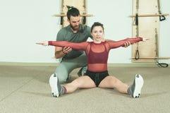与帮助年轻健身女孩的胡子的英俊的男性个人教练员在坚硬训练锻炼, selecti以后舒展她的肌肉 免版税库存照片