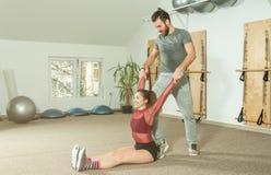 与帮助年轻健身女孩的胡子的英俊的男性个人教练员在坚硬训练锻炼, selecti以后舒展她的肌肉 免版税库存图片
