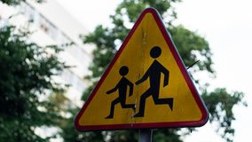 与帮助横跨街道的成人的图片的一个红色和黄色标志一个孩子 库存照片