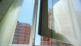 与帷幕和天空和城市的看法的窗口 屋子和开放Windows的概念性故事 股票视频