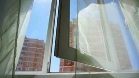 与帷幕和天空和城市的看法的窗口 屋子和开放Windows的概念性故事 股票录像