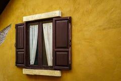 与帷幕的木窗口在破裂的黄色墙壁上 免版税库存图片