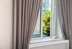 与帷幕的现代窗口在屋子里 被设计的家庭内部居住的减速火箭的空间样式 免版税库存照片