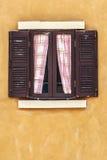 与帷幕的老布朗窗口在黄色墙壁,拷贝空间上 库存图片