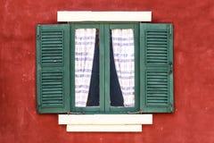 与帷幕的老绿色窗口在红色墙壁上 免版税库存图片