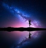 与常设女子实践的瑜伽的剪影的银河 库存图片