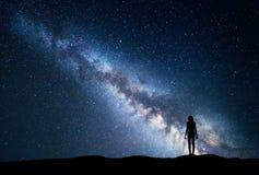 与常设妇女的银河 背景美好的图象安装横向晚上照片表使用 免版税图库摄影