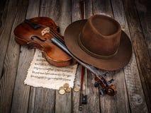 与帽子、小提琴和硬币的静物画 免版税库存照片