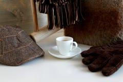 与帽子、手套和围巾的浓咖啡咖啡在白色桌上 免版税库存图片