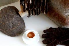 与帽子、手套和围巾的浓咖啡咖啡在白色桌上 免版税库存照片
