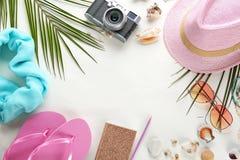 与帽子、照相机和海滩的平的位置构成在白色背景反对 库存照片