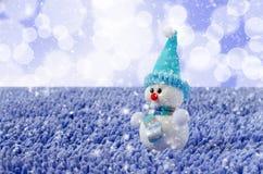 与帽子和围巾的玩具雪人 落的雪 免版税库存照片