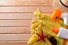 与帽子和太阳镜的两朵浪花suncream在木板条 免版税图库摄影