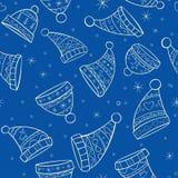 与帽子的冬天无缝的样式在蓝色backgrou 库存图片
