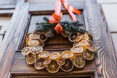 与干切片的圣诞节花圈在老门的桔子 库存图片