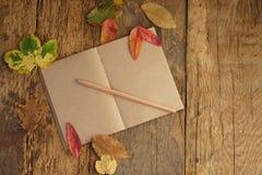 与干叶子和笔记本的秋天模板 图库摄影