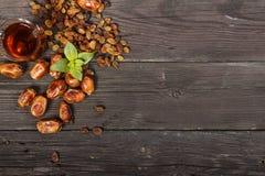 与干旱时期的传统阿拉伯,土耳其语赖买丹月在一张木黑桌上的茶和葡萄干 ramadan 土耳其新鲜的茶与日期 免版税库存照片